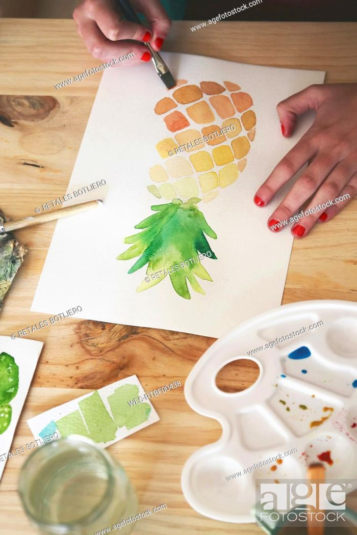 Stock Photo: Woman's hand painting aquarelle of a pineapple at desk in her studio.