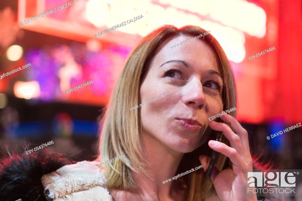 Stock Photo: Young blonde pretty woman talking on phone in the city centre at night. Red neon lights in the background .
