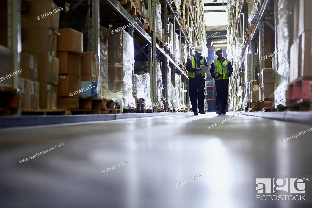 Stock Photo: Workers walking in distribution warehouse aisle.