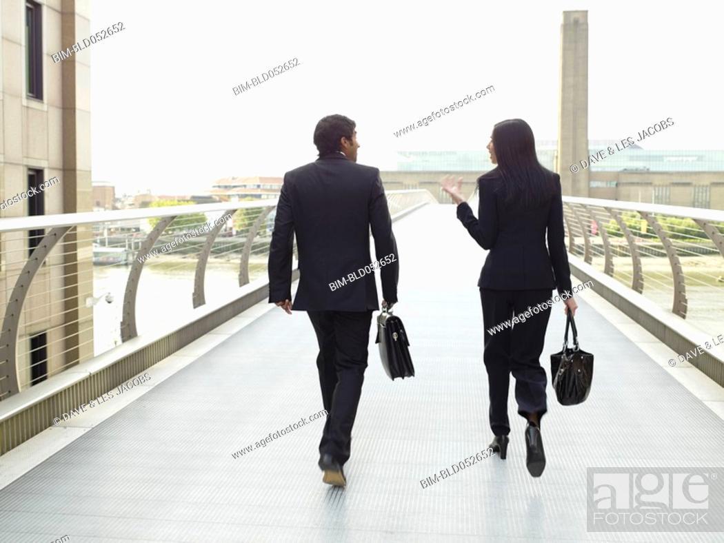 Stock Photo: Multi-ethnic businesspeople walking on skyway.