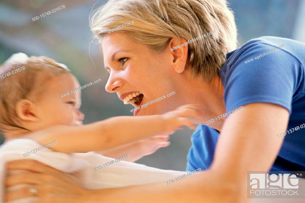 Stock Photo: Side profile of a mother holding her baby boy.