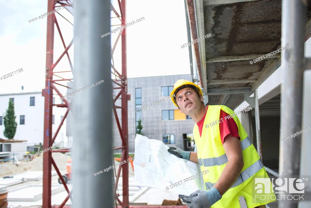 Stock Photo: Construction worker holding blueprint at construction site.