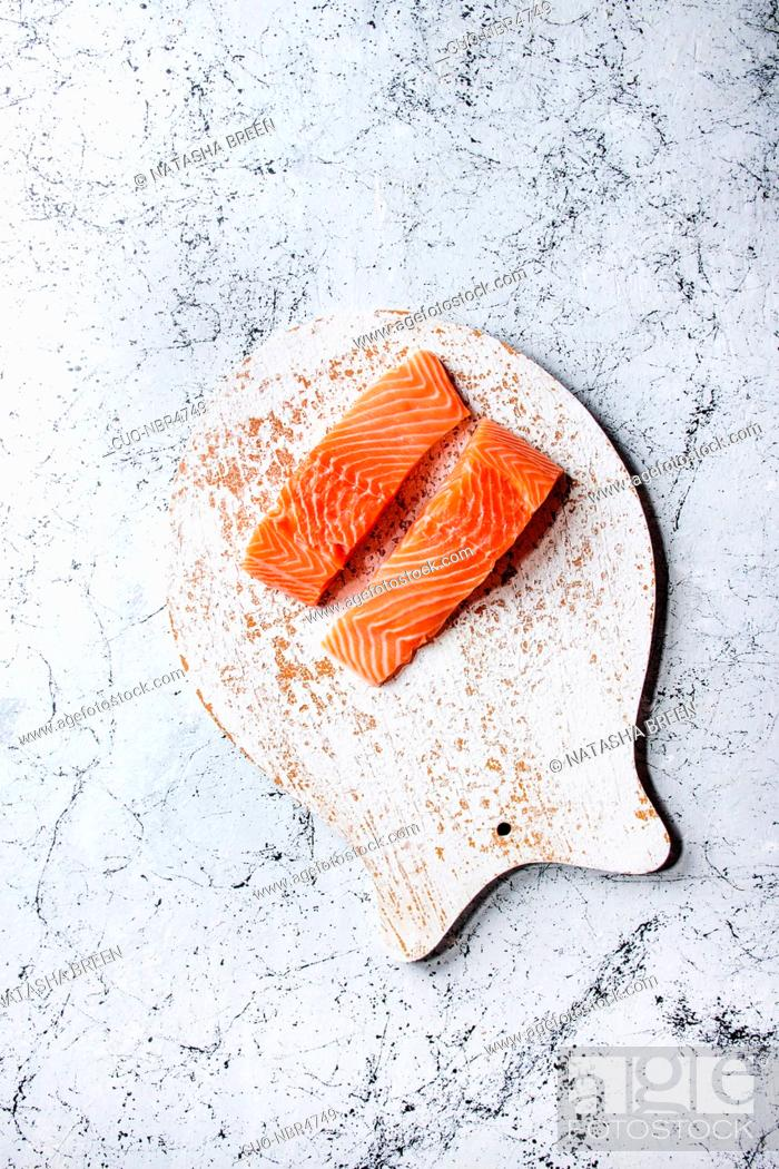 Stock Photo: Sliced raw uncooked salmon fillet on wooden chopping board as fish shape with sea salt and pepper over white marble texture background.