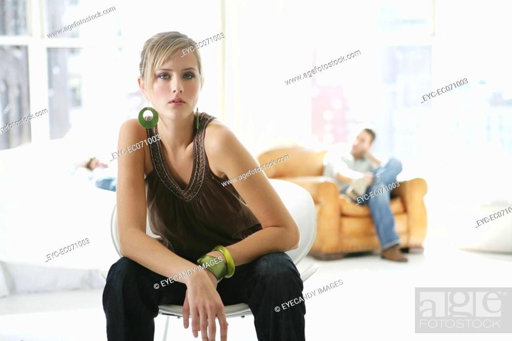Stock Photo: Portrait of young woman sitting with man in background.