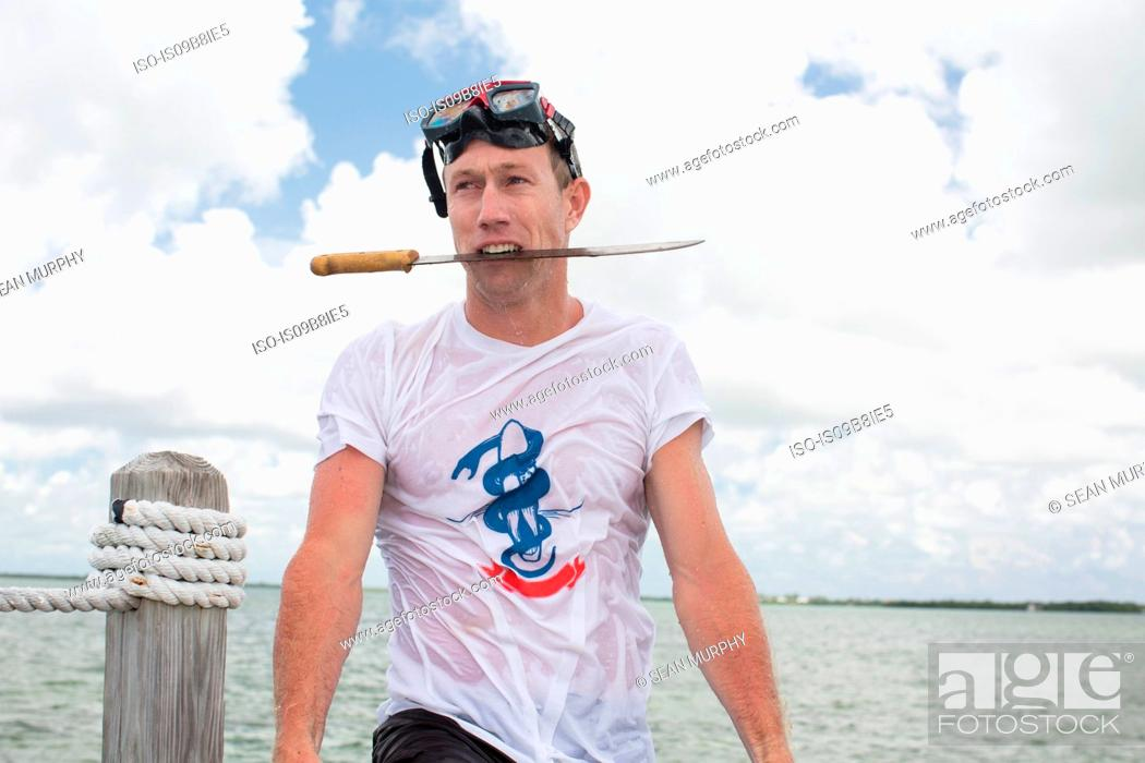 Stock Photo: Man beside water, holding knife in mouth.