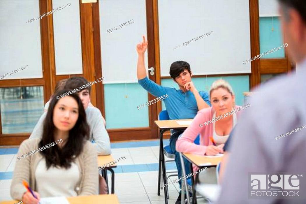 Imagen: Student raising hand to ask question in college classroom.