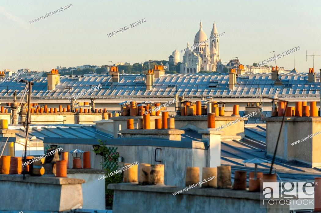 Stock Photo: France, Paris, Le Sacre Coeur in the distance on the hill of Montmartre, emerges above the roofs and chimneys North of the city (aerial view).