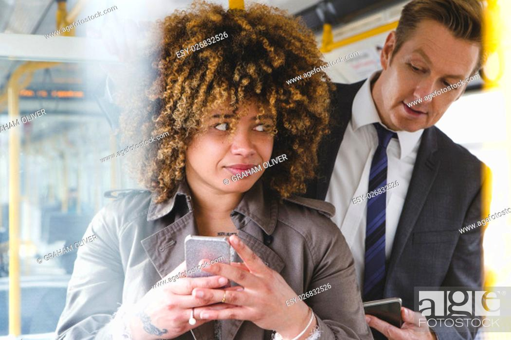 Stock Photo: Man looking over a womans shoulder on the train at her phone screen.