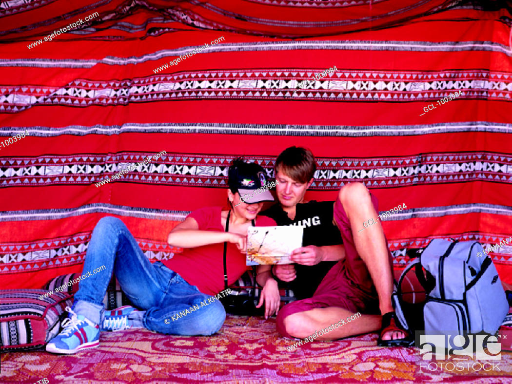 Stock Photo: Western tourist couple sitting in Arabian tent reading a map, United Arab Emirates.