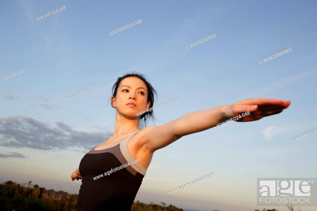 Stock Photo: Low angle view of a young woman exercising.