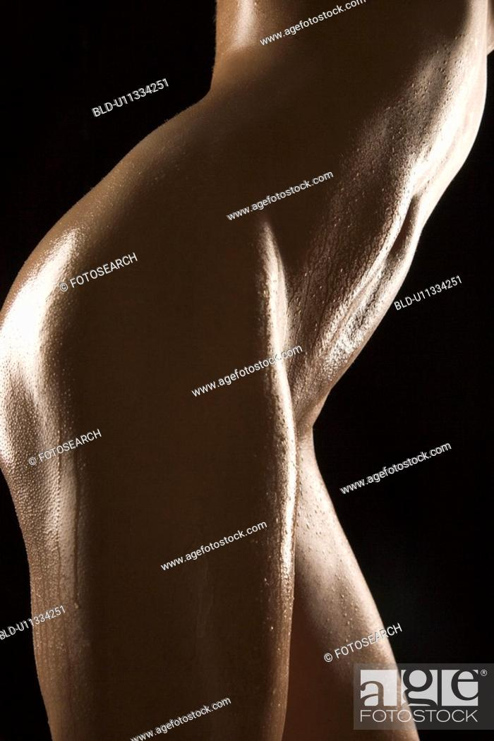 Stock Photo: Side view of thighs and stomach of nude adult woman glistening with body oil.