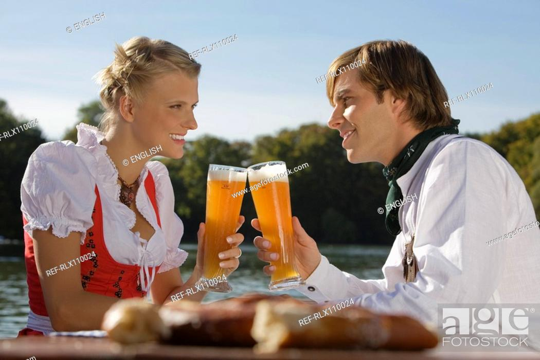 Stock Photo: Young couple in traditional Bavarian outfit, sitting in beer garden, Munich,.