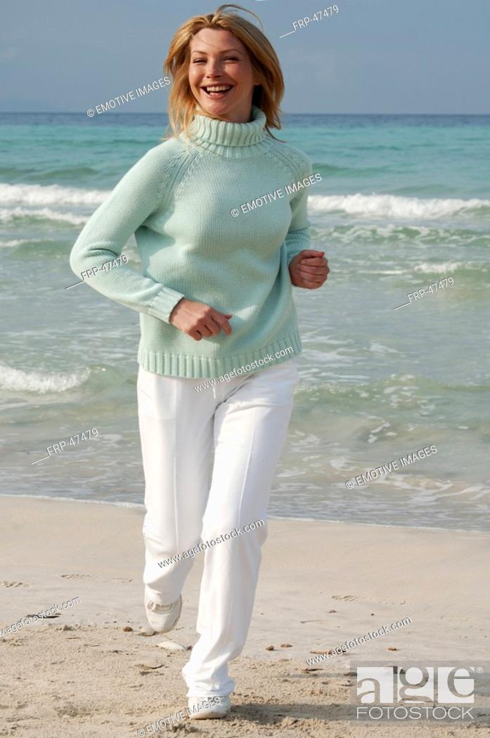 Stock Photo: Jogging woman in turquoise sweater at the sea.