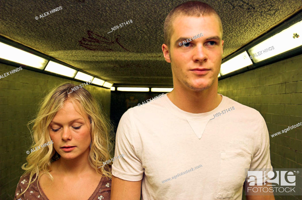 Stock Photo: Attractive young couple moving through city underground passage.
