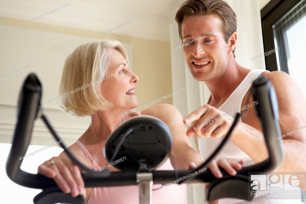Stock Photo: Senior Woman On Exercise Bike With Trainer.