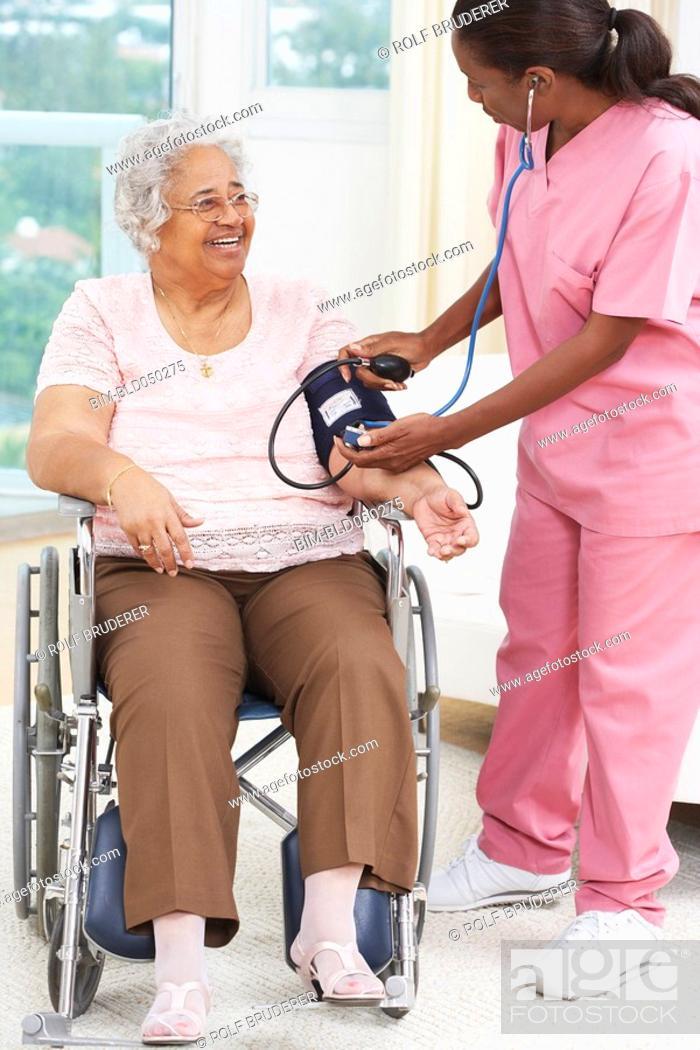 Stock Photo: Nurse taking senior woman's blood pressure.