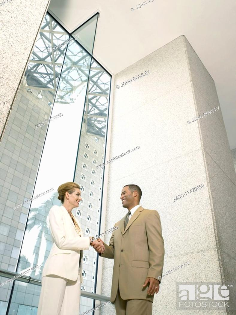 Stock Photo: Businesspeople shaking hands in office building low angle view.