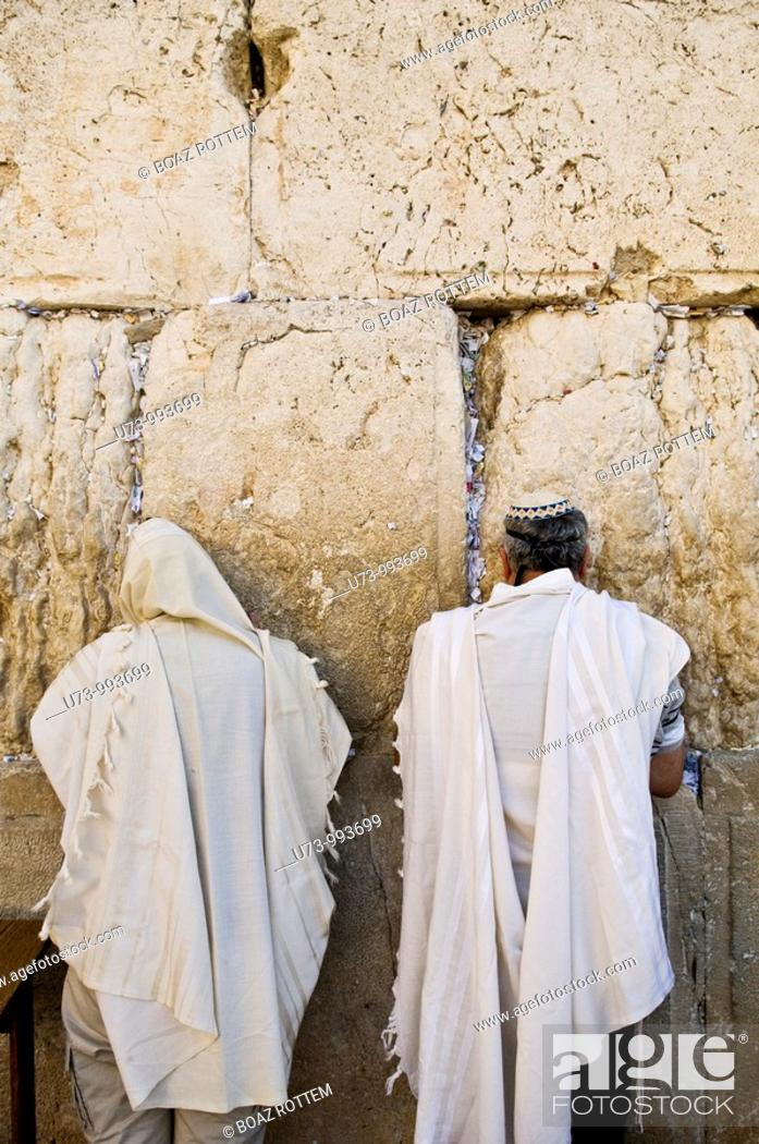 Stock Photo: Two Jewish men pray at the holy wailing wall in the old city of Jerusalem.Jews believe that the wailing wall is the western wall of the Jewish temple which was.