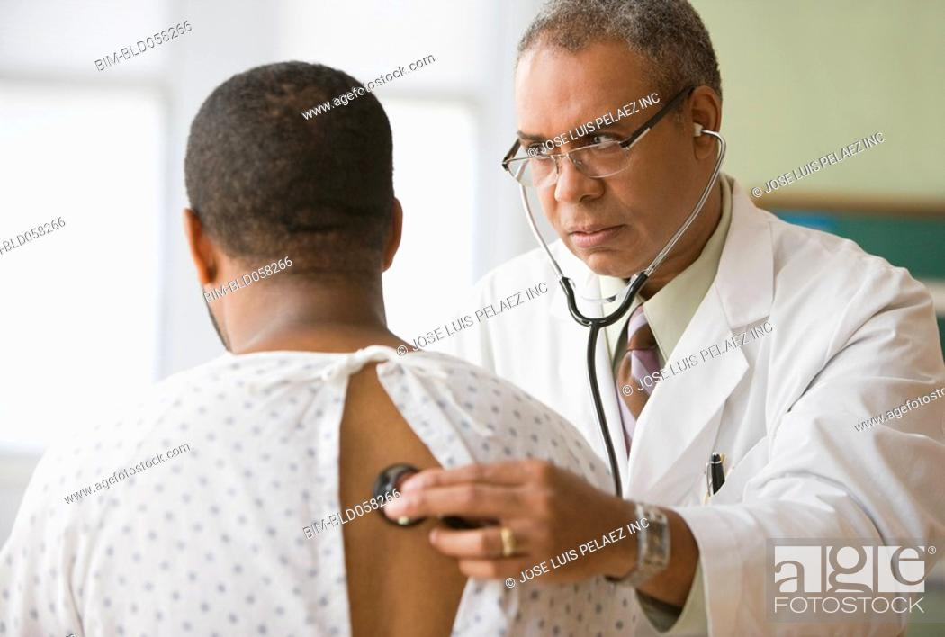 Stock Photo: African male doctor examining patient.