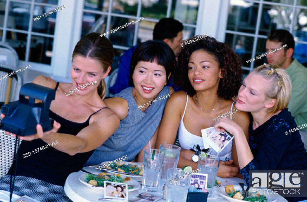 Stock Photo: Four young women photographing themselves in a cafe.