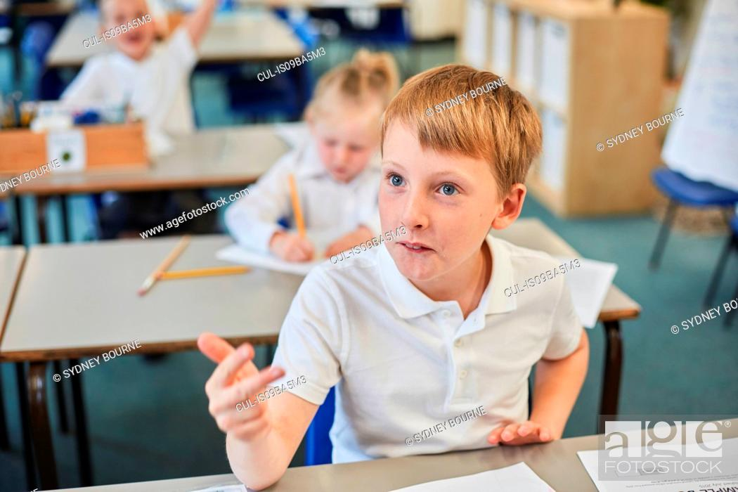 Stock Photo: Schoolboy counting with fingers in classroom at primary school.