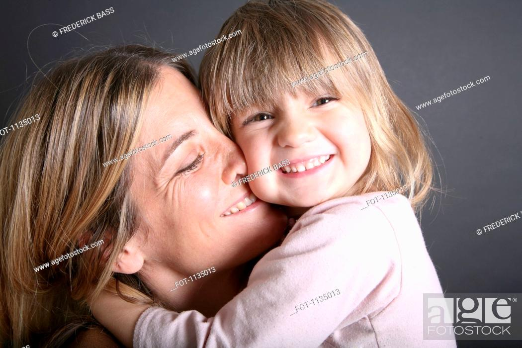 Stock Photo: A smiling young girl hugging her mother, close-up.