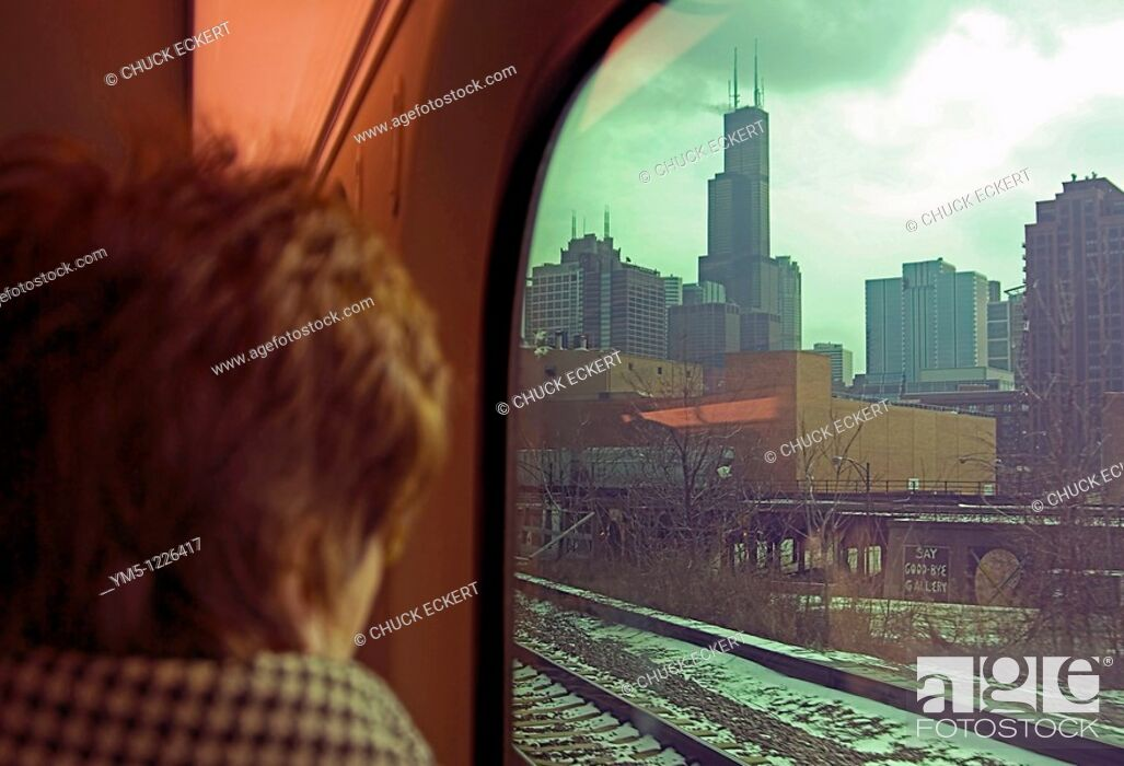 Stock Photo: Woman looking out Metra train window at the Sears Tower Willis Tower on her way into Chicago.