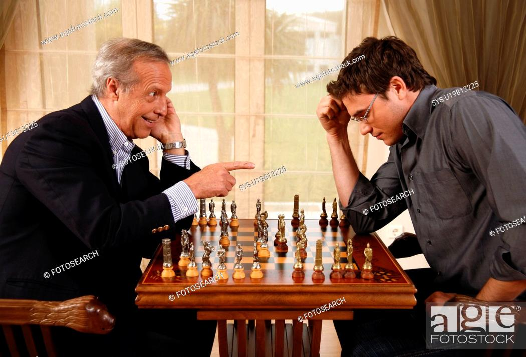Stock Photo: Mature man and younger man playing chess.
