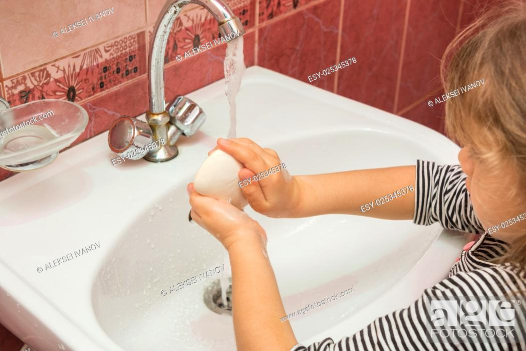 Stock Photo: Five-year girl soaps hands with soap in the sink.