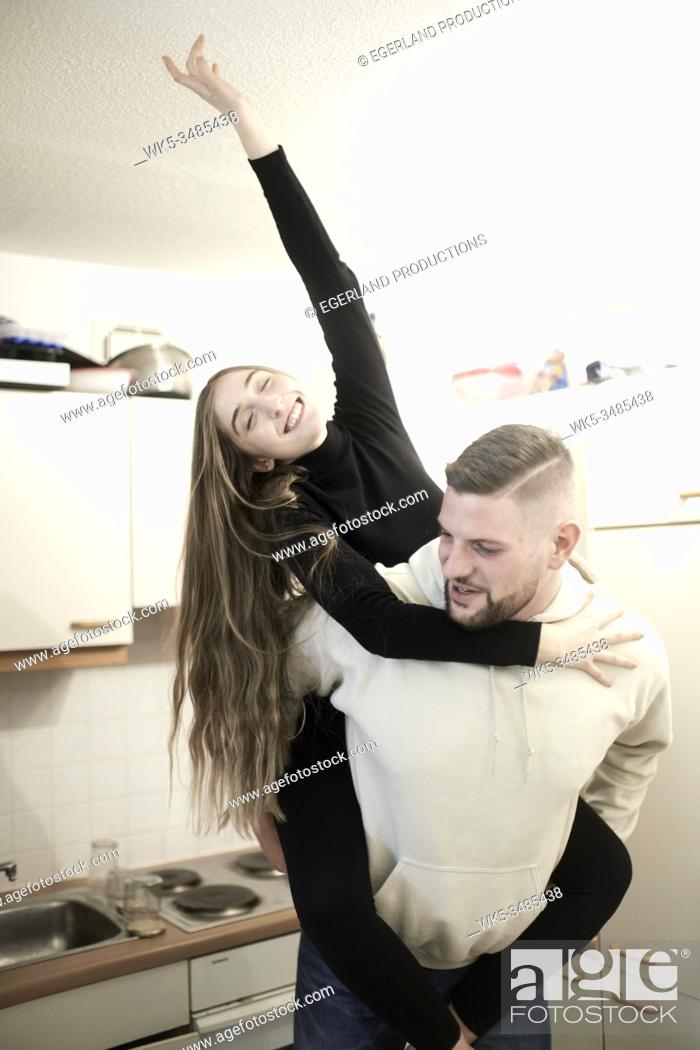 Imagen: happy girlfriend piggyback on boyfriend in kitchen.