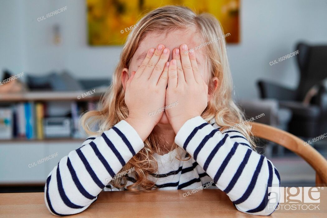 Stock Photo: Portrait of young girl, sitting at table, covering face with hands.