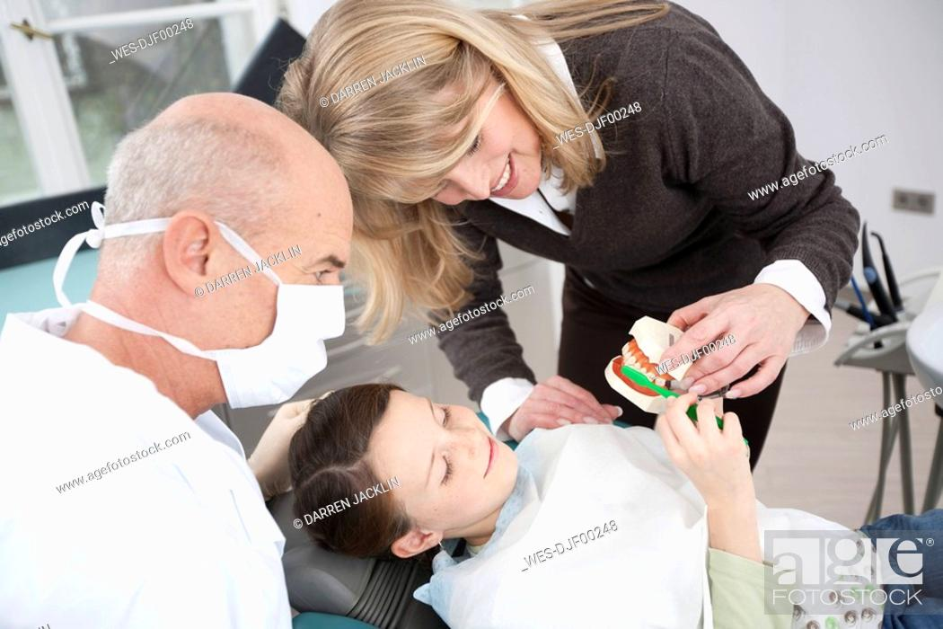 Stock Photo: Germany, Bavaria, Landsberg, Mother showing girl 8-9 how to brush teeth, dentist beside.