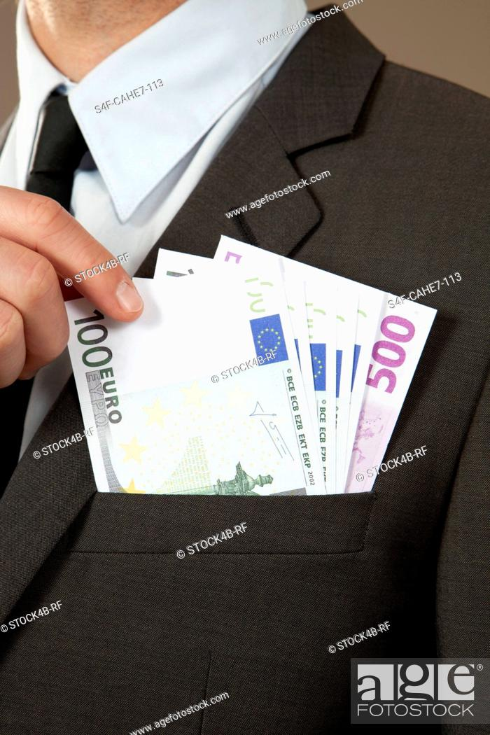 Stock Photo: Businessman grasping in jacket pocket with Euro notes.