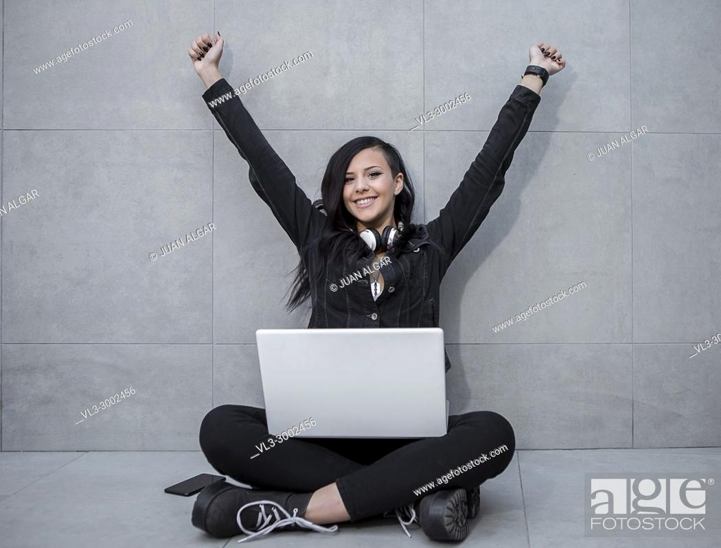 Stock Photo: Smiling casual woman sitting with laptop and celebrating with hands up while looking at camera.