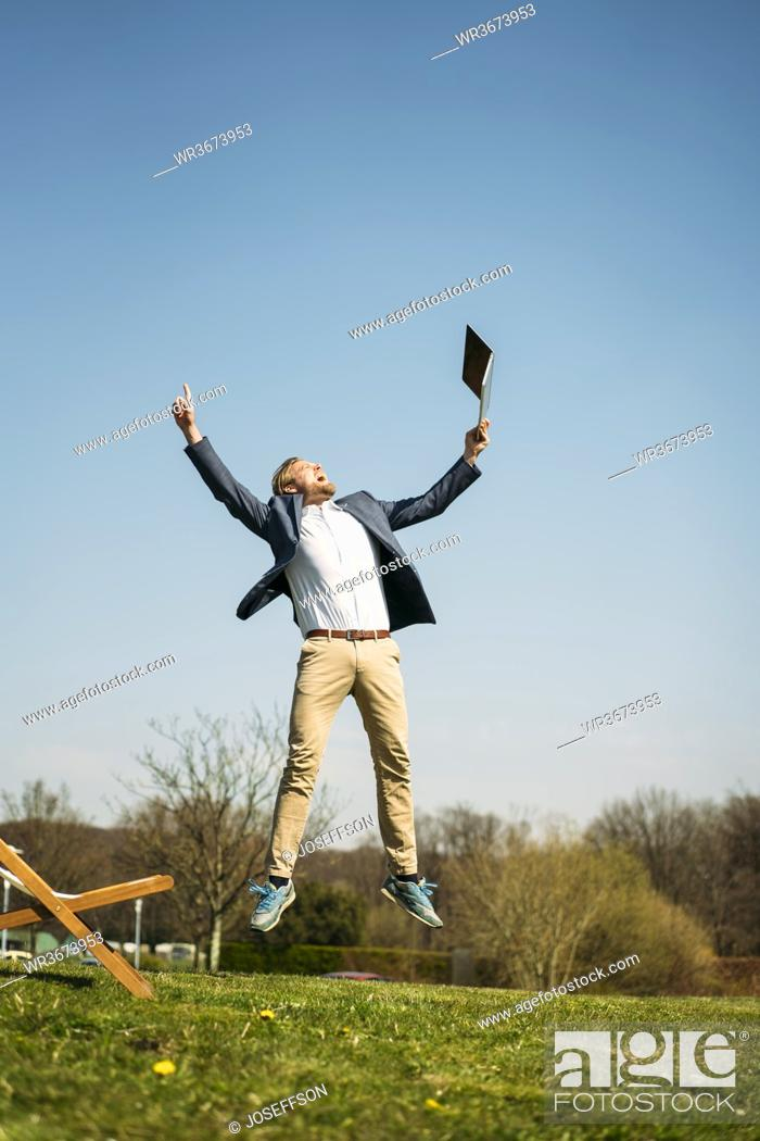 Stock Photo: Excited businessman holding laptop while jumping on grass at park against clear sky during sunny summer day.