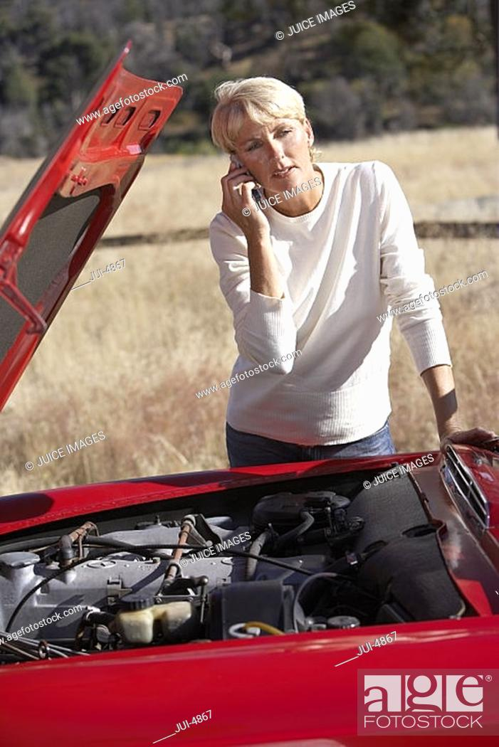 Stock Photo: Woman standing beside red convertible car with engine trouble, using mobile phone.