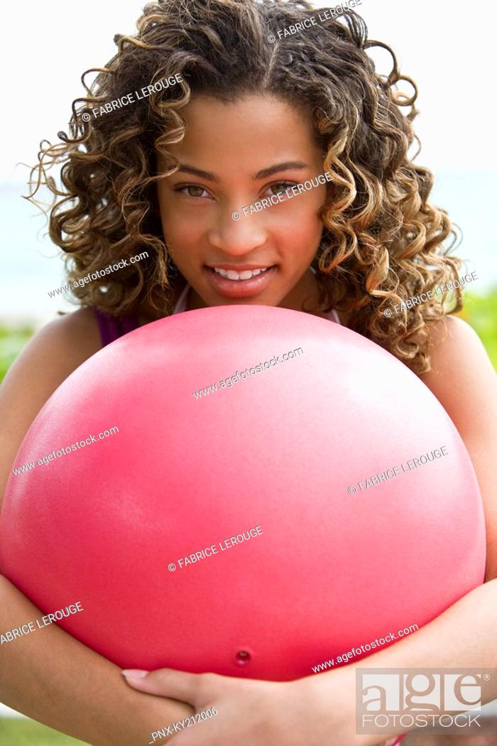 Stock Photo: Portrait of a girl hugging a ball and smiling.