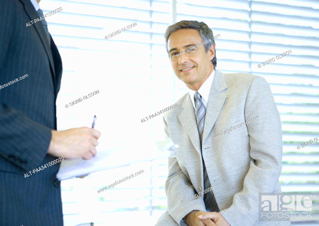 Stock Photo: Businessman smiling at camera while colleague signs document.