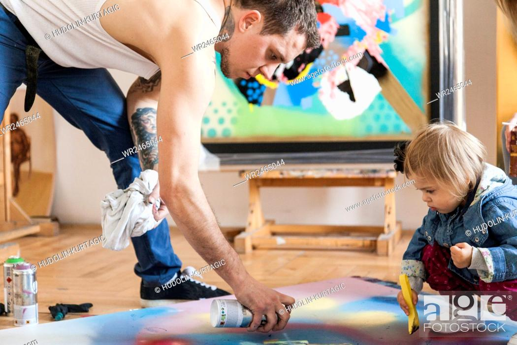 Stock Photo: Male painter and toddler girl creating painted art work together.