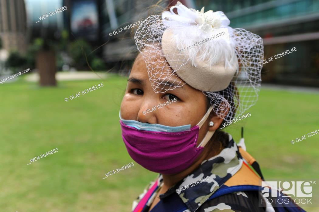 Imagen: Singapore, Republic of Singapore, Asia - Portrait of a woman who covers her face with a protective face mask to protect herself and others against an infection.
