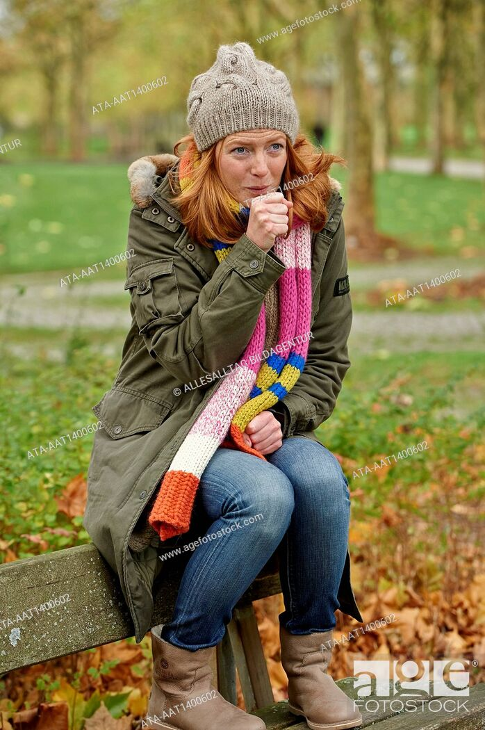 Stock Photo: Coughing woman sitting outside on a park bench.