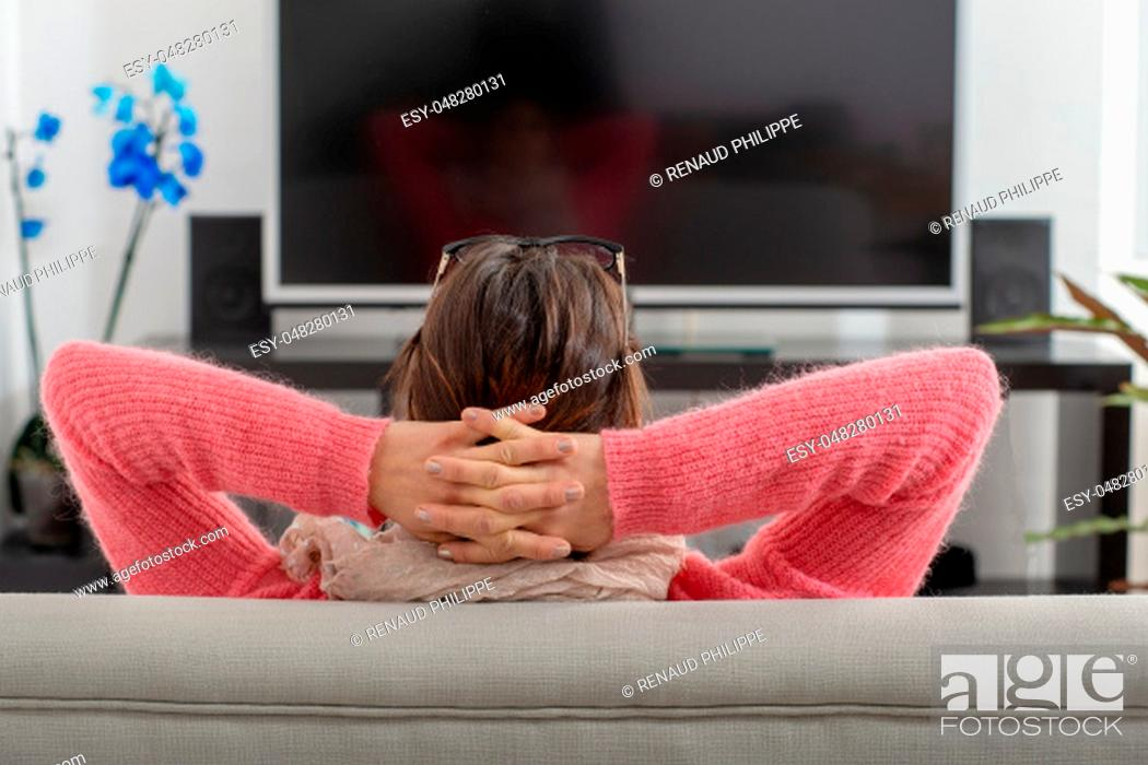 Stock Photo: a back view of a young brunette woman watching TV.