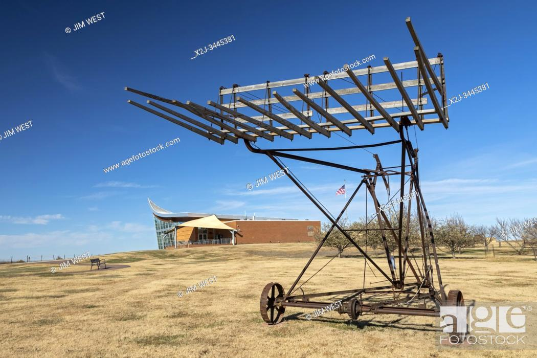 Stock Photo: Beatrice, Nebraska - Homestead National Monument. A piece of old farm machinery is displayed outside the Heritage Center.