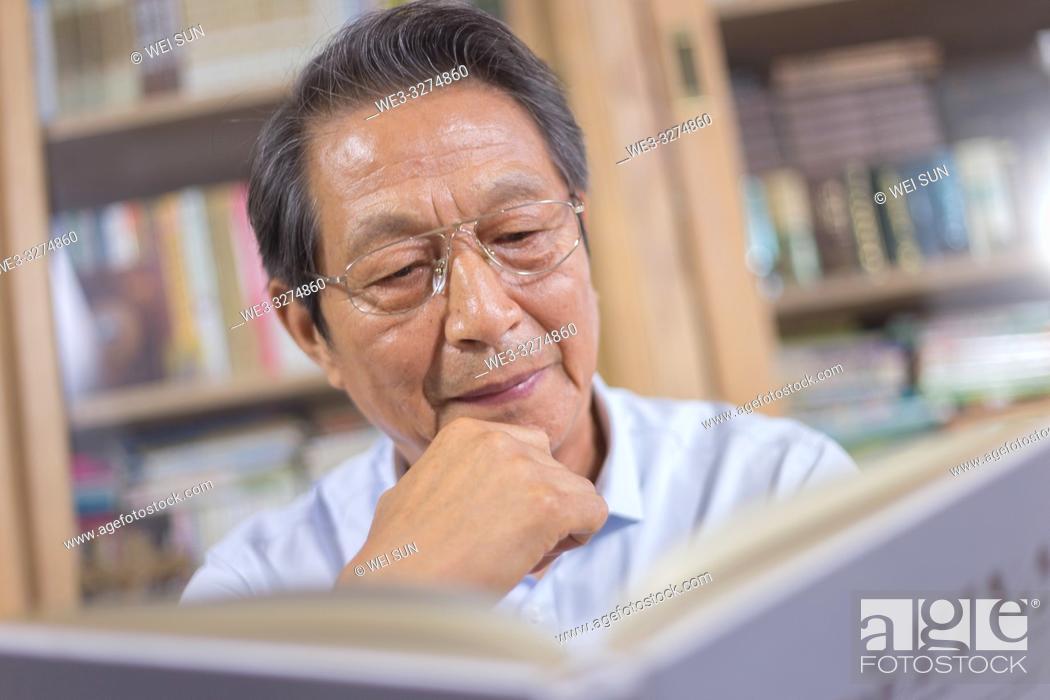 Stock Photo: Elderly man reading book.