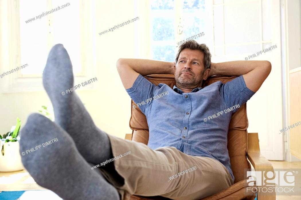 Stock Photo: Man sitting in arm chair with feet up, daydreaming.