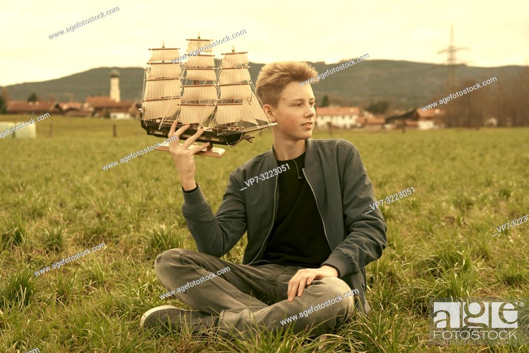Photo de stock: male teenager holding ship while sitting outdoors on meadow at countryside, travel lust, pensive mood, in Waakirchen, Bavaria, Germany.