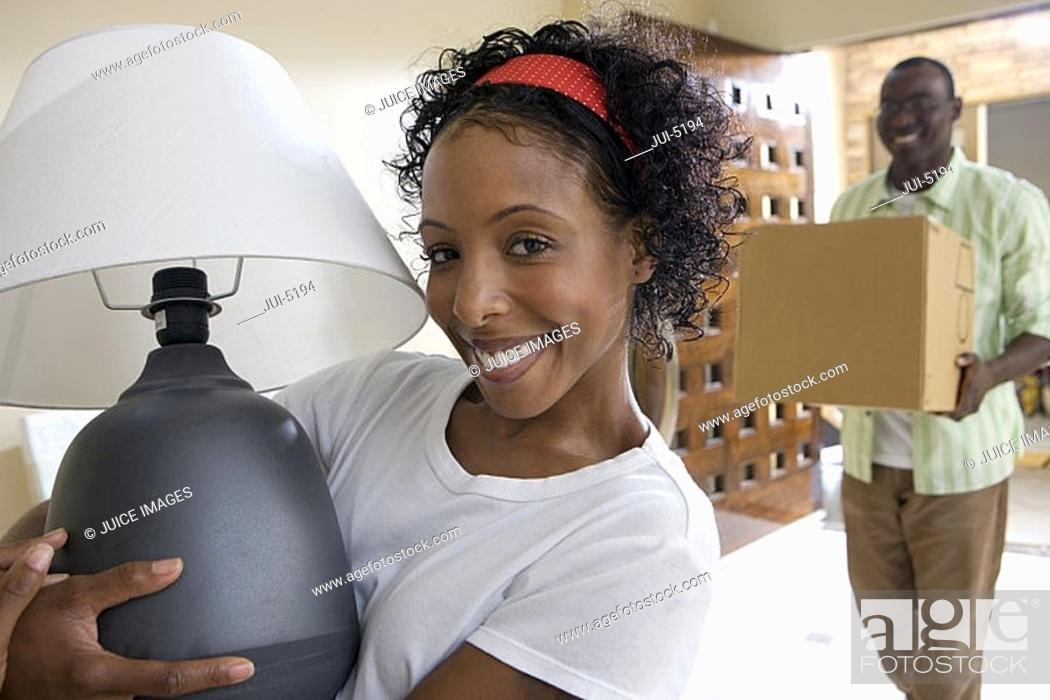 Stock Photo: Couple moving house, man carrying box in hallway, woman holding lamp, smiling, portrait.