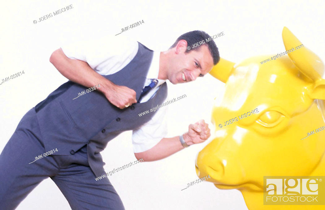 Stock Photo: Studio picture of a young man, businessman, 25-30 30-35 35-40 years old, wearing a white shirt and a waistcoat, fighting with a yellow bull.