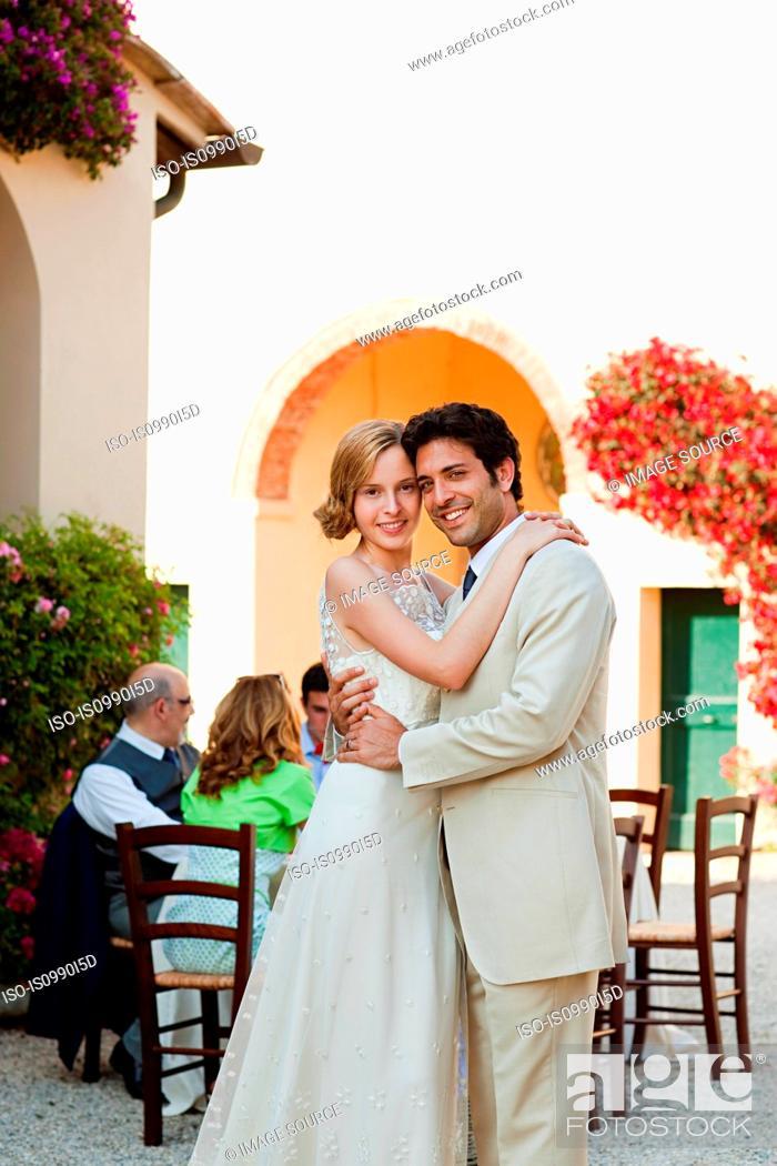 Stock Photo: Newlyweds embracing at wedding reception.