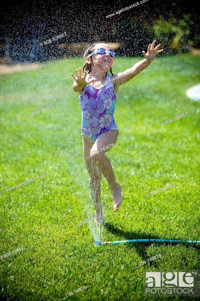 Stock Photo: Young girl leaps through yard sprinkler.